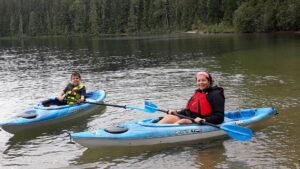 Mom and young son sitting in their blue kayaks on Priest Lake.