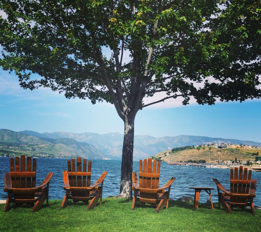 Four Adirondack chairs facing out towards the blue water of Lake Chelan.