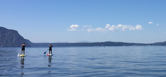 Two people stand-up paddling on the flat water of Lake Pend Oreille.