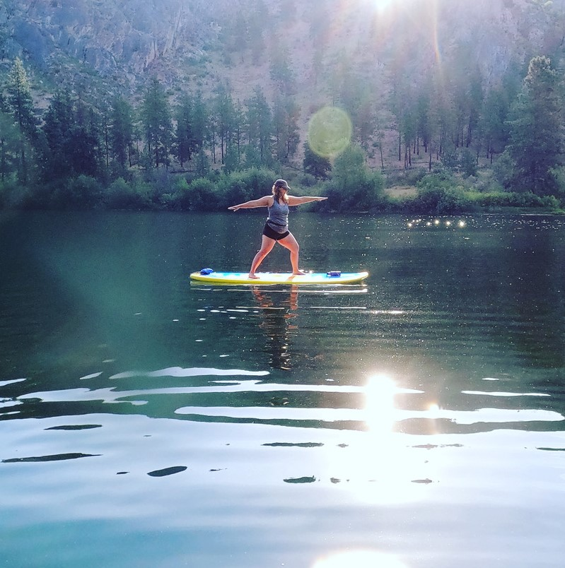 Woman doing a yoga pose while on a stand-up paddleboard on a lake.