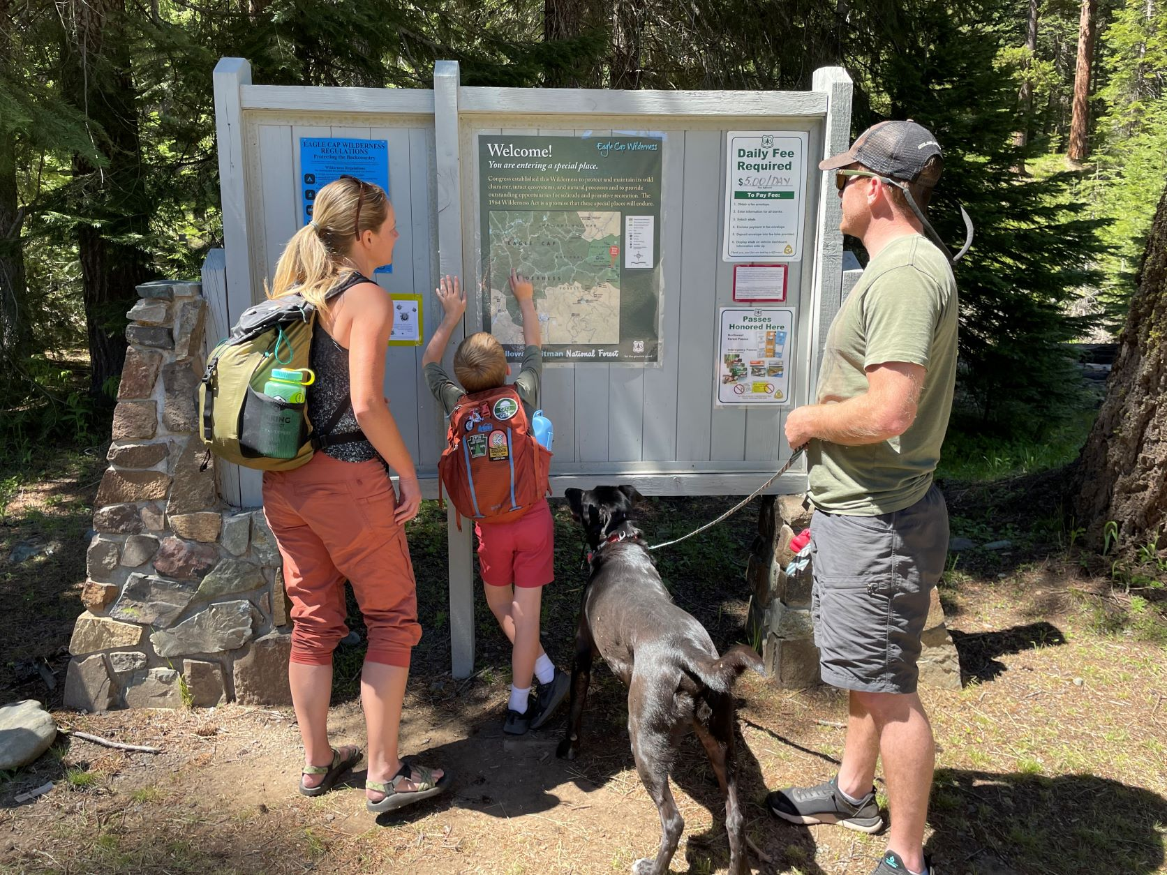 Child reading a trail map at a trailhead kiosk with two adults looking on.