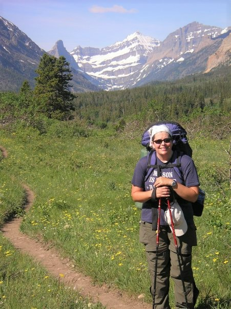 Writer backpacking in Glacier National Park, on a singletrack trail through a meadow with a mountain peak in the distance.