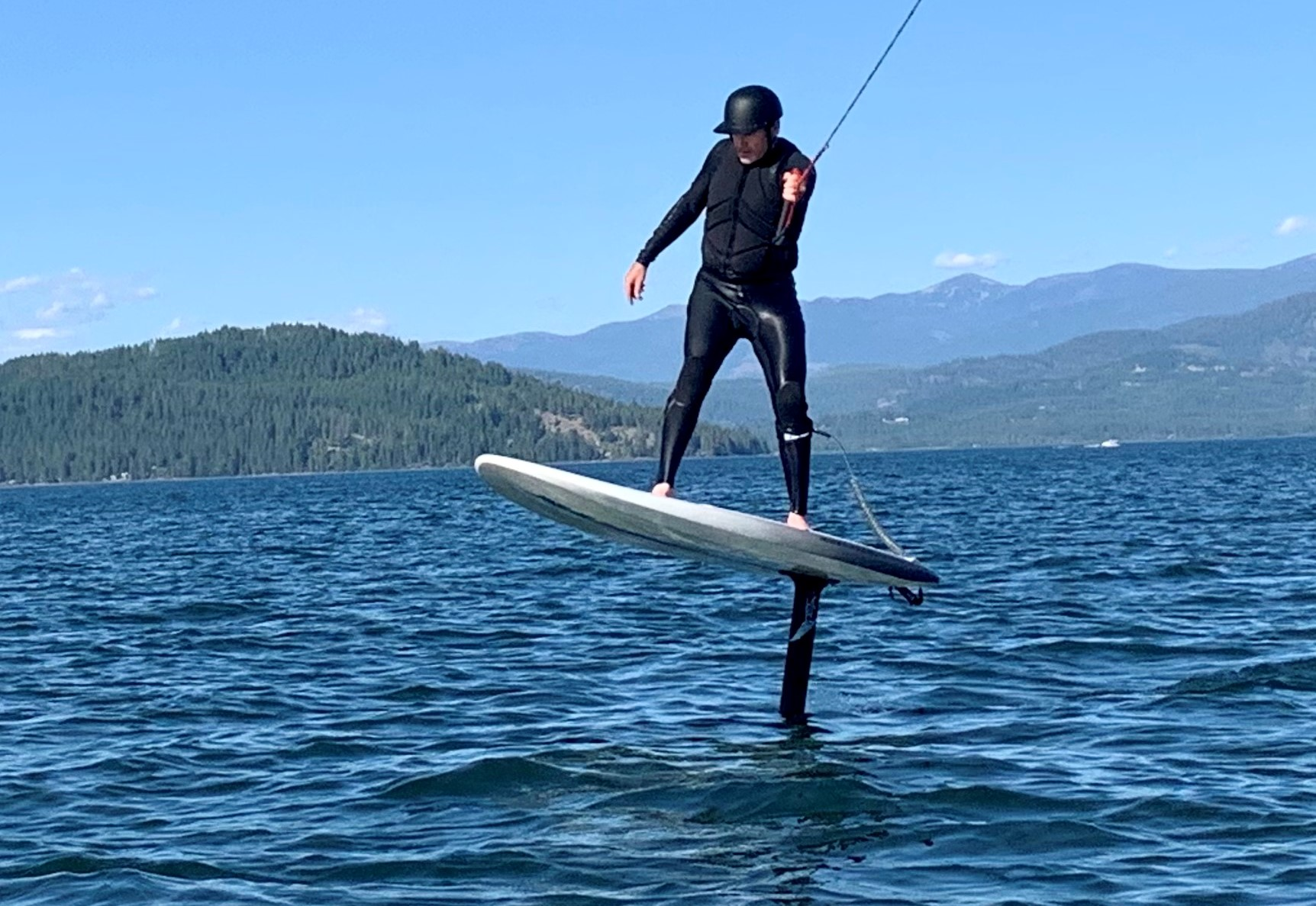 Man standing on wind foiling board, getting towed behind power boat, on Lake Pend Oreille.