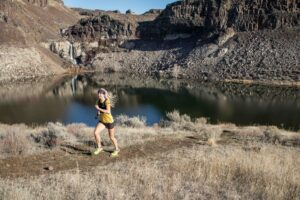 Runner on a dirt trail in the wilderness.