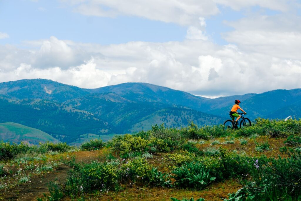 Mountain biker riding along a singletrack trail on a ridge with distance peaks in the background.