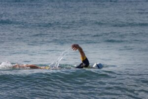 Swimming doing freestyle strokes in open water, wearing a wetsuit, swim cap, and goggles.