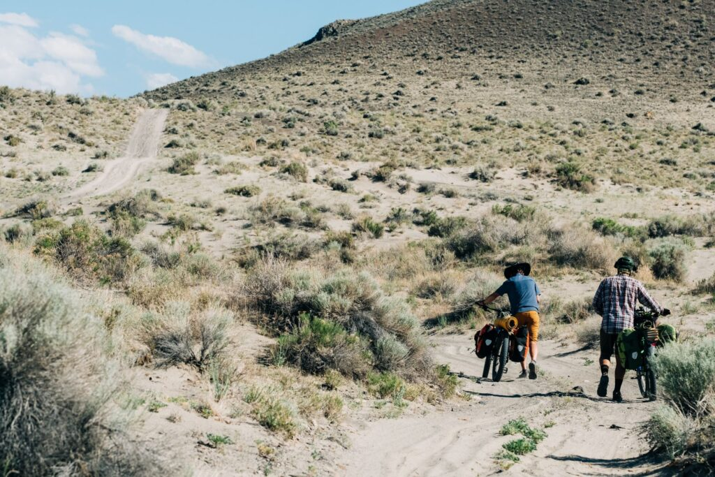 Two bikers pushing their bikes, loaded with bikepacking gear, through the sadn drifts of Big Sand Gap in Oregon.