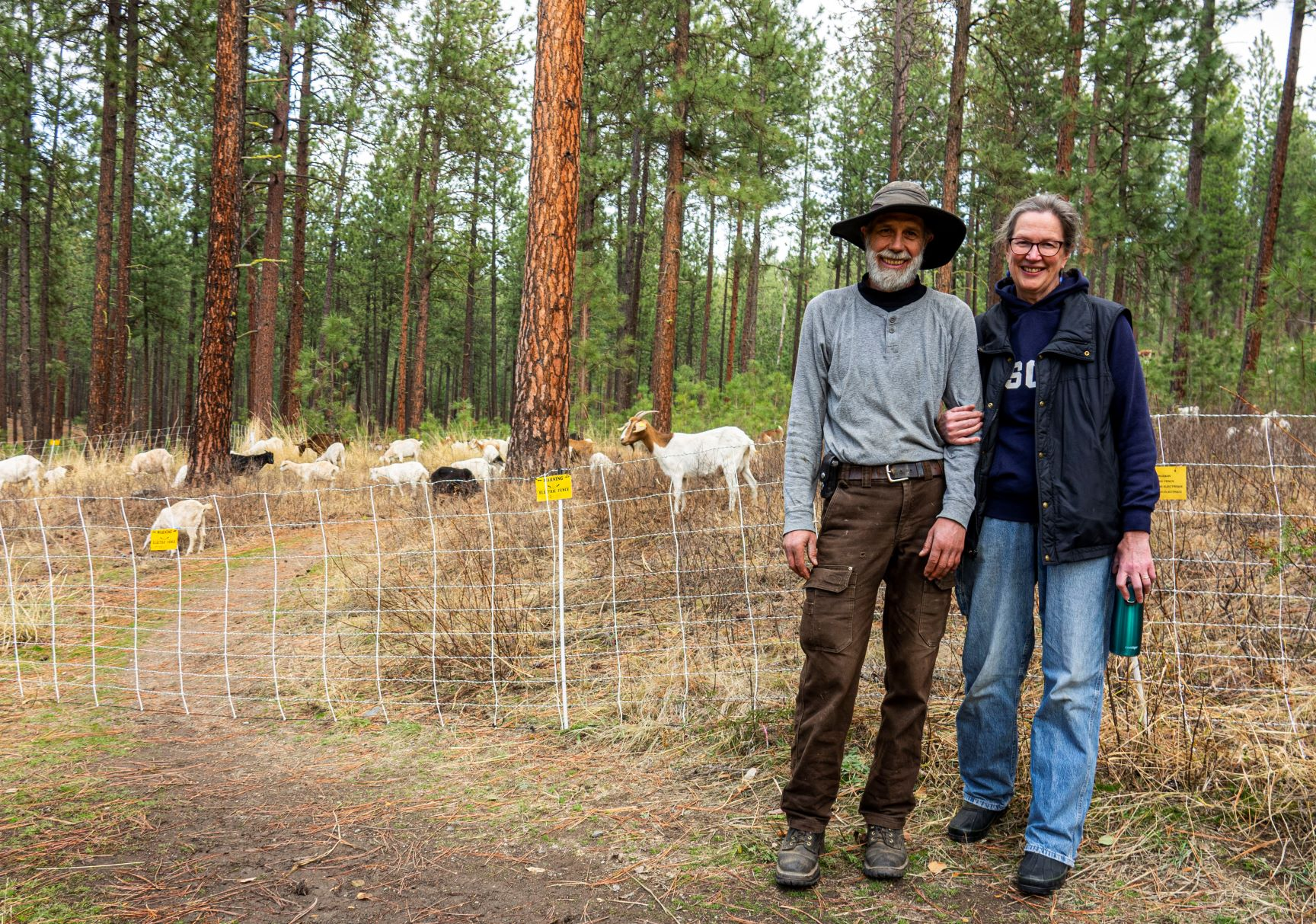 Healing Hooves goat shepherds standing near the fence enclosure with their grazing goats on Spokane's High Drive Bluff.