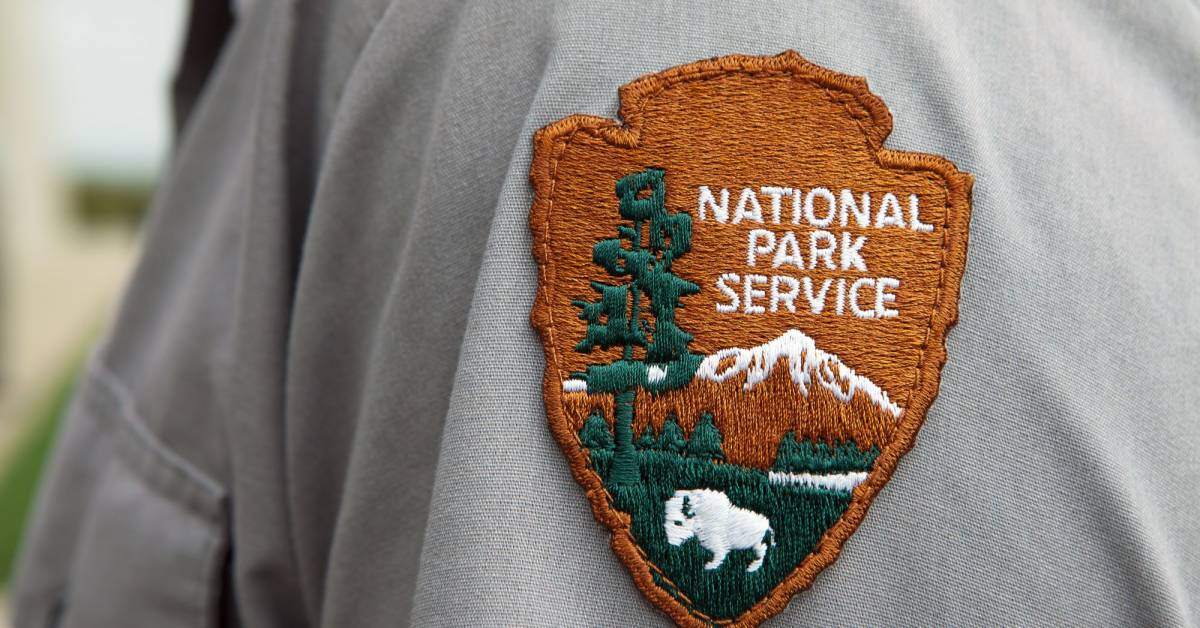 National Park Service patch, brown with green pine tree and snowy mountain peak, on the sleeve of a park ranger.