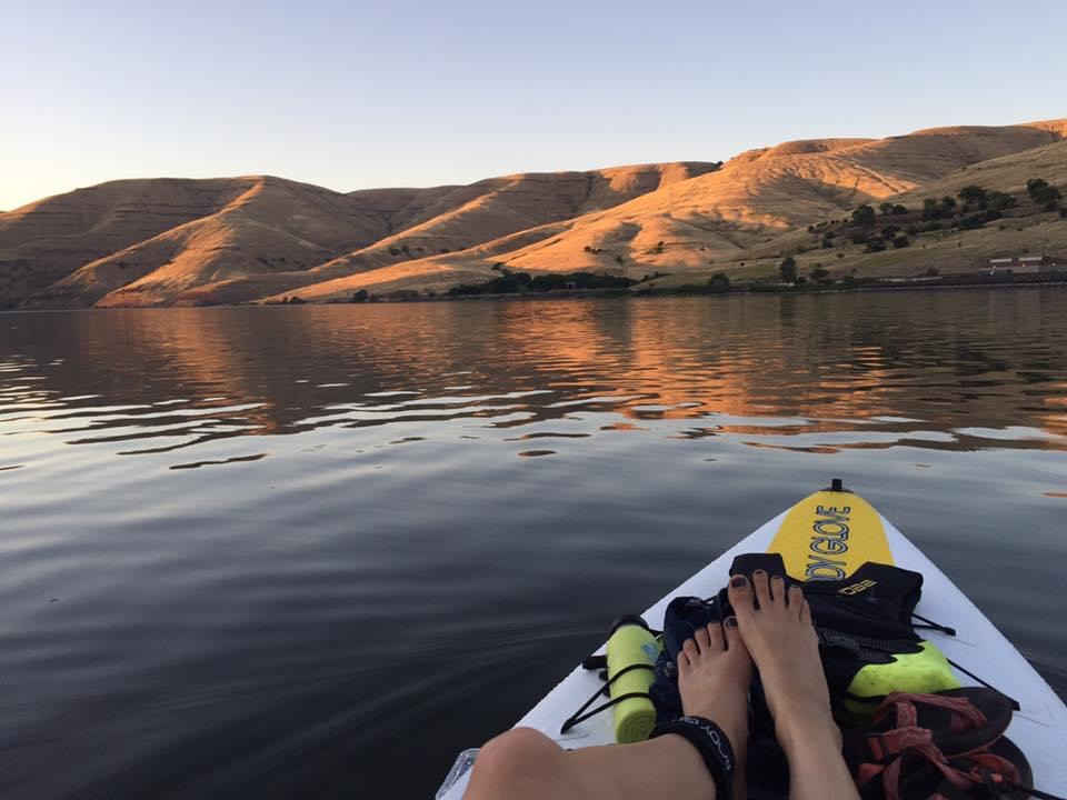 Paddler's view of the glowing Snake River, during sunset, with the sloping hills and paddler's feet resting on her paddleboard.