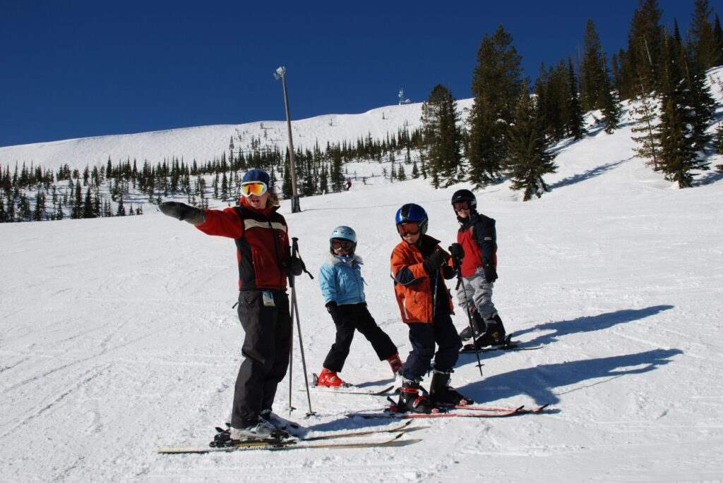 Ski instructor pointing downhill while teaching a group of three young skiers at Schweitzer Mountain.