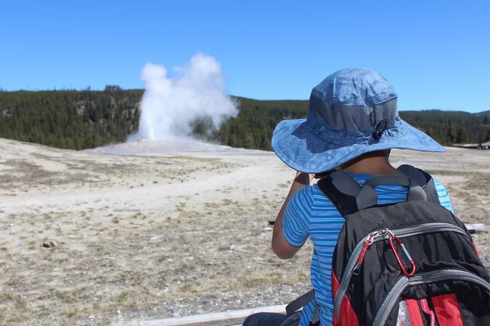 Child observing a thermal feature, steam rising from the ground, at Yellowstone National Park.